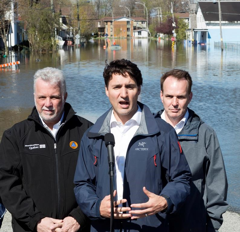 Quebec Premier Philippe Couillard and Gatineau MP Steve McKinnon look on as Canadian Prime Minister Justin Trudeau speaks to media following a tour of a flooded area of Gatineau, Que. Thursday May 11, 2017. Photo by the Canadian Press/Adrian Wyld