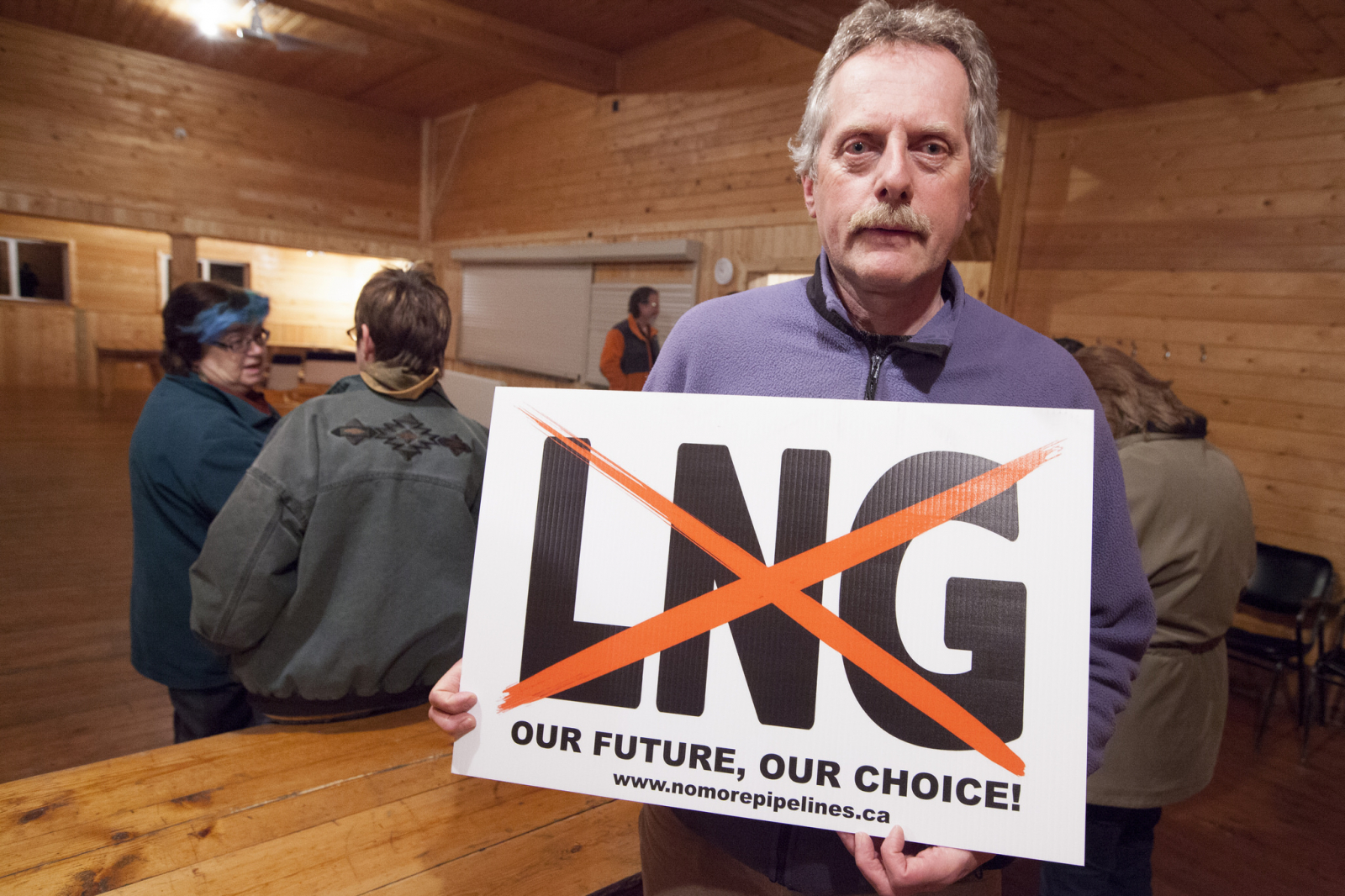 "Paramedic Graeme Pole holding a ""No LNG"" sign seen on lawns and road sides throughout the Kispiox Valley - Photo by Mychaylo Prystupa"