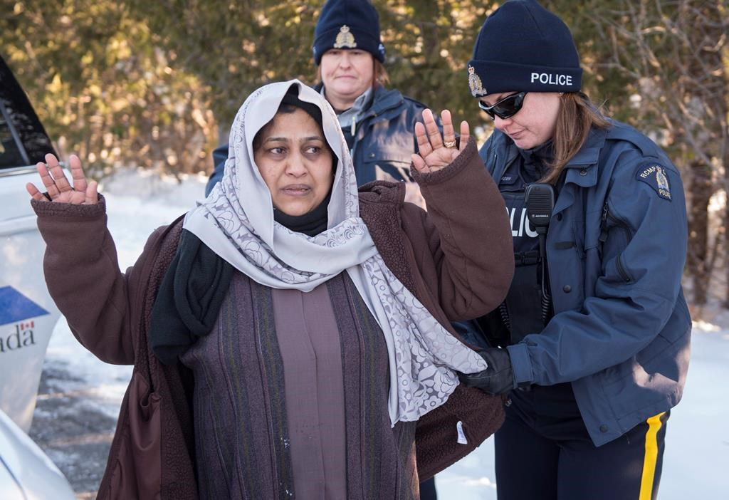 An RCMP officer frisks as asylum claimant after crossing the border into Canada from the United States with her two daughters,  Friday, March 17, 2017 near Hemmingford,