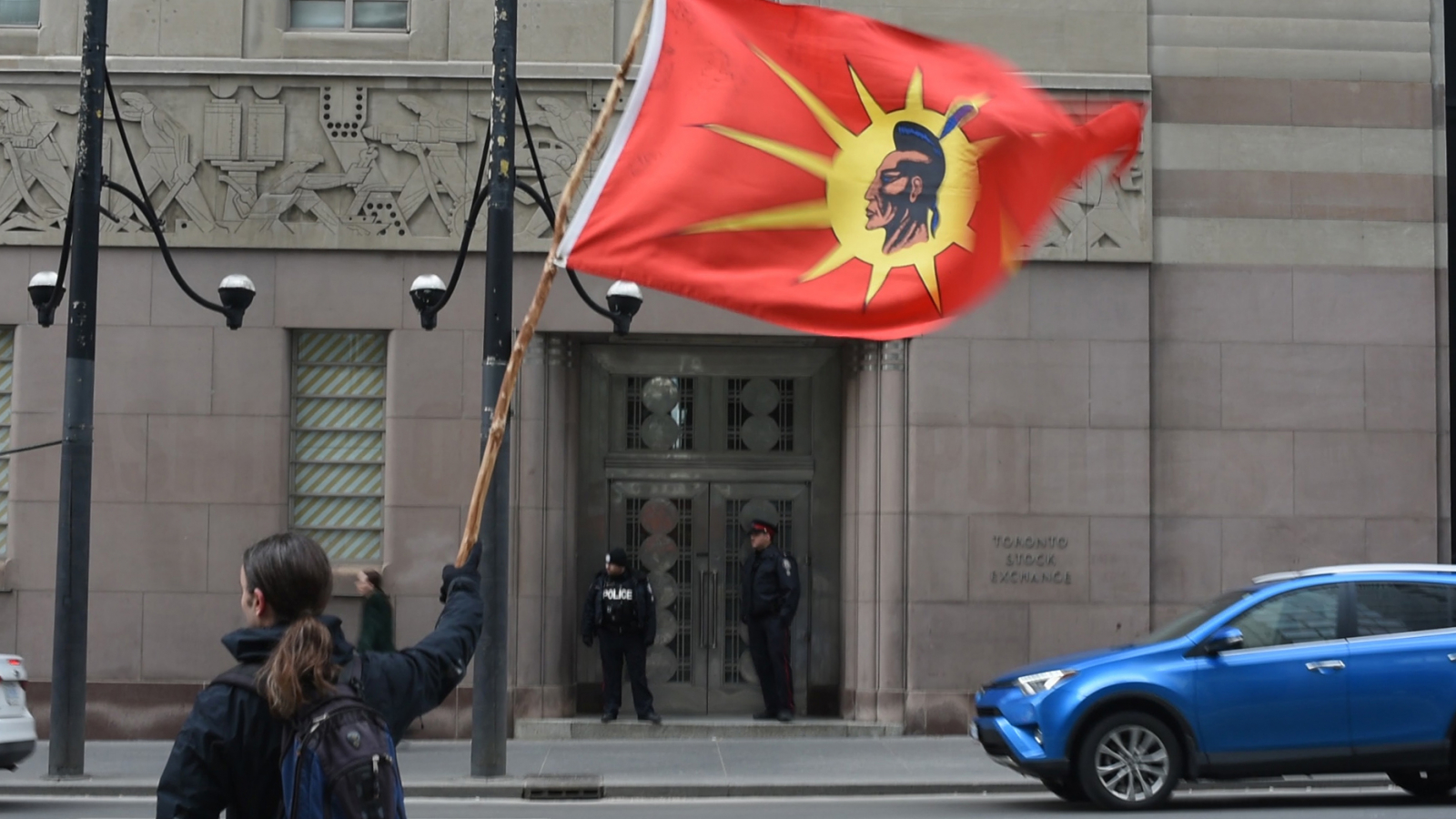 A man waves the Mohawk Warrior Society flag at a protest outside TD Bank's headquarters in downtown Toronto on March 30, 2017, to demand that the company end its partnership with Kinder Morgan. Photo by National Observer.