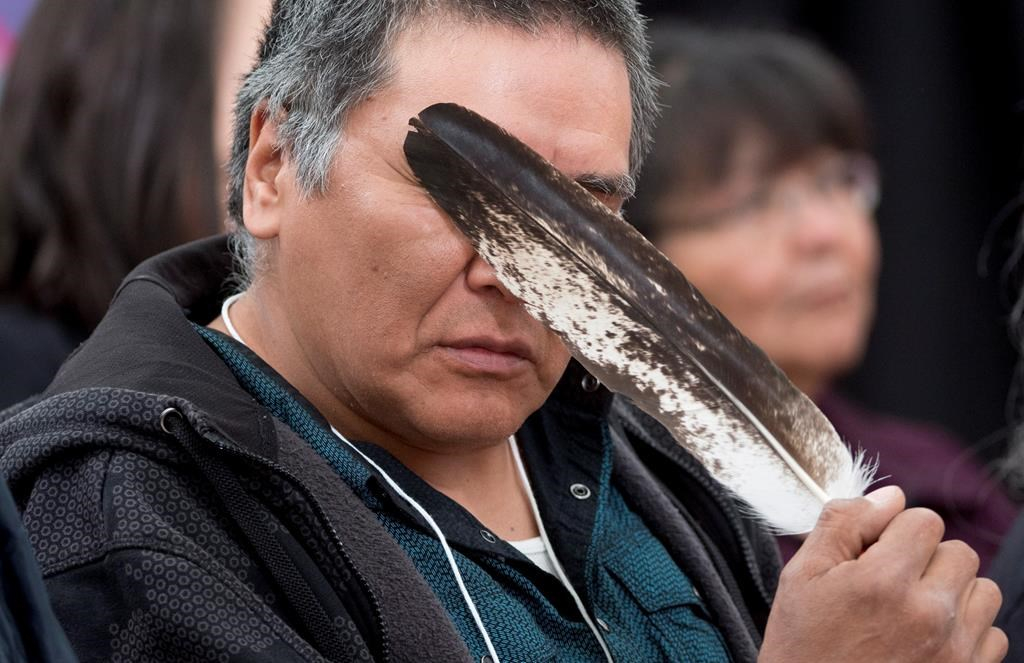 Terry Ladue holds a eagle feather to his face after speaking of his mother Jane Dick Ladue's murder at the National Inquiry into Missing and Murdered Indigenous Women and Girls taking place in Whitehorse on June 1, 2017.