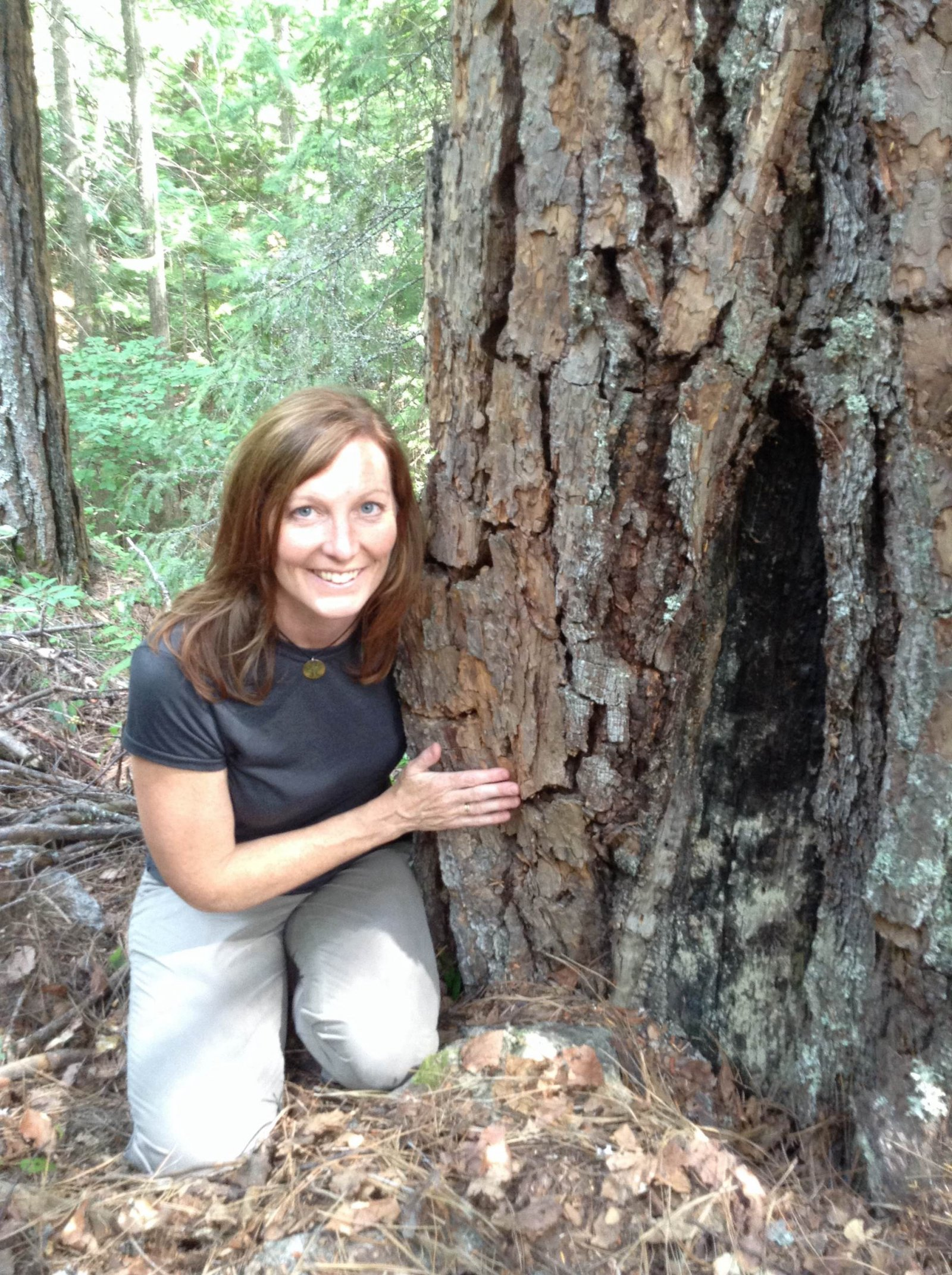 Lori Daniels, a professor of forest ecology at the University of British Columbia, poses beside a fire-scarred pine tree.