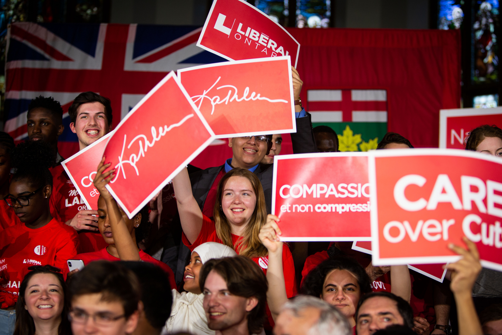 Ontario Liberal supporters hold up campaign signs, including