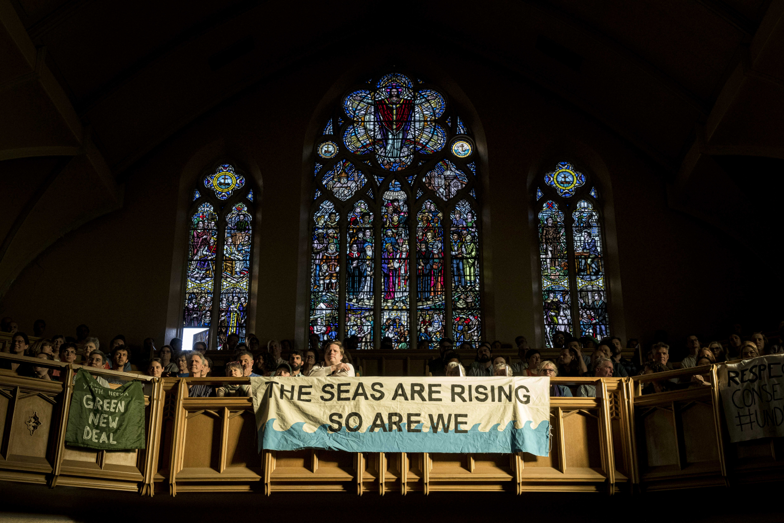People who attended a town hall on climate change in Toronto dropped banners expressing their concern over rising sea levels. Photo by Chris Katsarov.