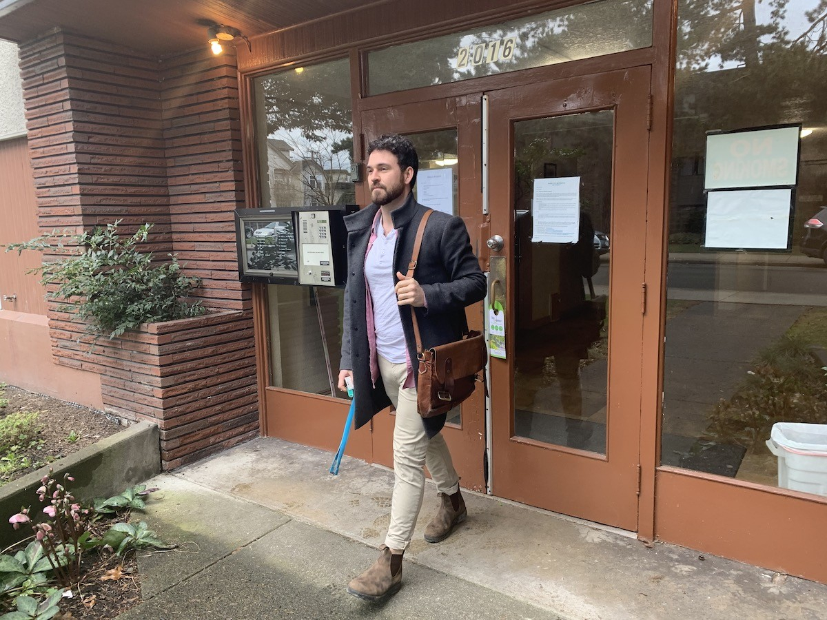 A man walks out of an apartment building carrying a messenger bag and a set of keys