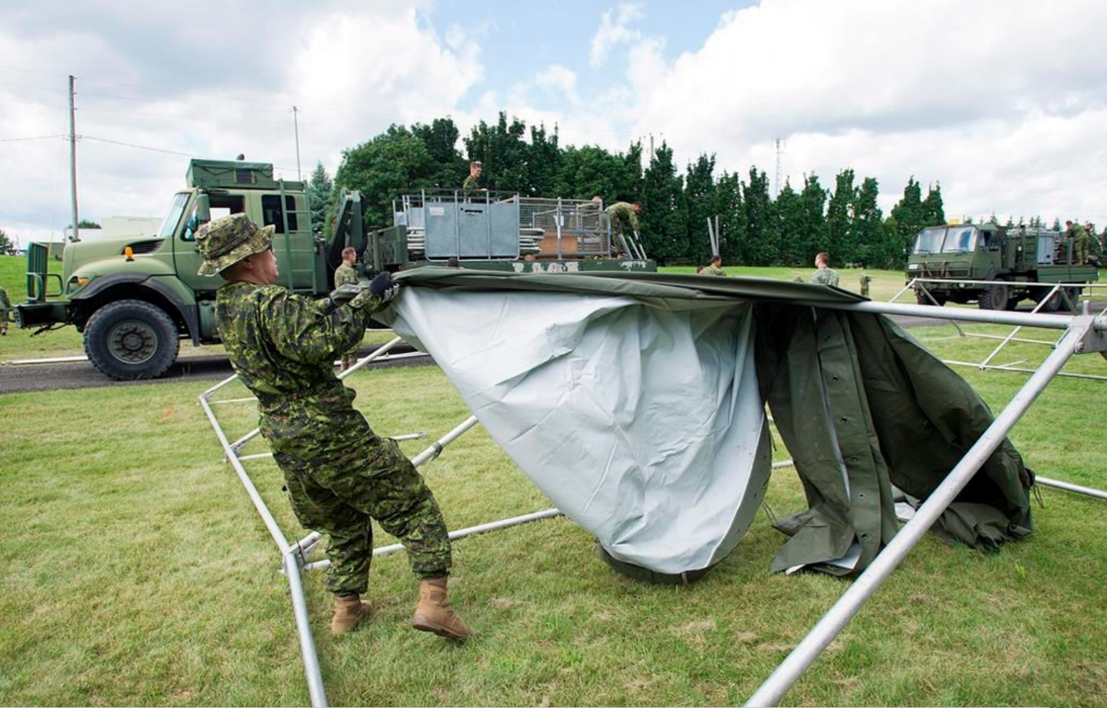 Members of the Canadian armed forces erect tents to house asylum seekers at the Canada-United States border in Lacolle Que. Wed. Aug. 9 2017. & About 100 soldiers help with the crush of asylum seekers at Quebec ...