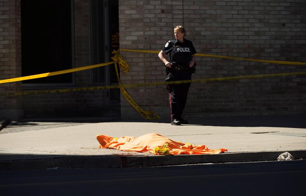 ebf608c241f9f4 A police officer stands over a covered body in Toronto after a van mounted  a sidewalk crashing into a number of pedestrians on Monday