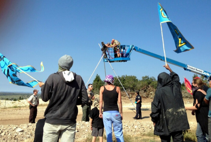 Police use cherry−pickers to remove protestors from the top of tripod-like blockades.