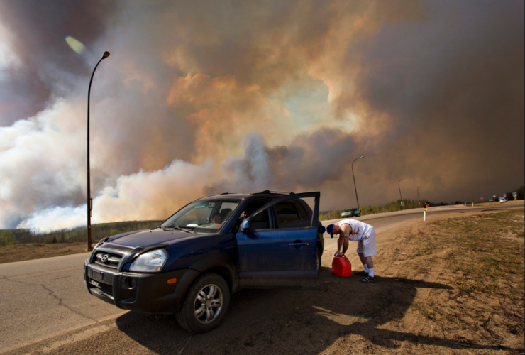 An evacuee puts gas in his car on his way out of Fort McMurray,. Photo from Jason Franson/Canadian Press