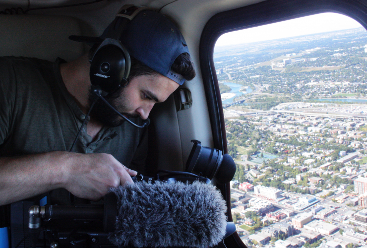 Film director Geordie Day shooting footage in a helicopter over Calgary. Photo from Geordie Day