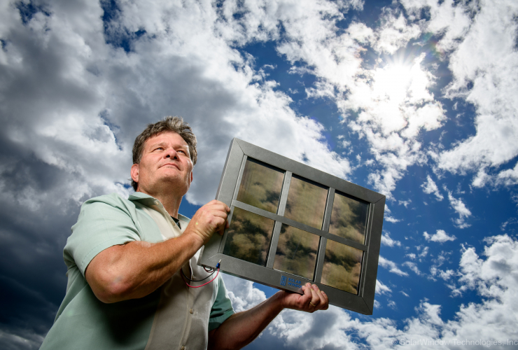 SolarWindow CEO John Conklin holds one of the company's specially coated windows. Photo by SolarWindow