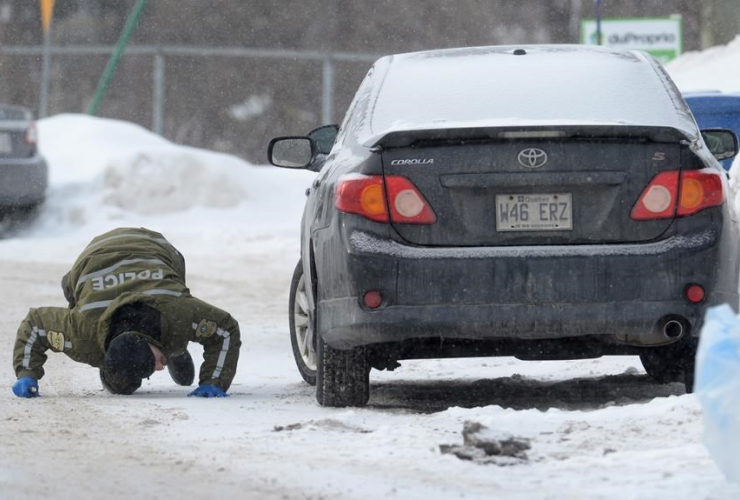 A police officer looks for evidence under a car near a Quebec City mosque on Monday January 30, 2017, where a shooting left six people dead and eight others injured Sunday. Photo by Paul Chiasson/CP.