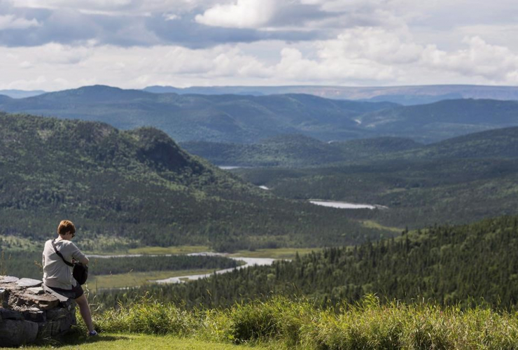 A German tourist looks out over Stuckless Pond in Gros Morne National Park, N.L.,