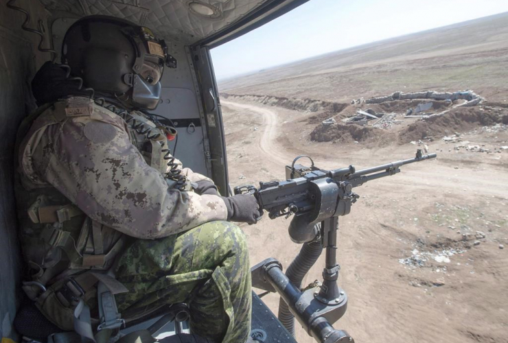 A Canadian Forces door gunner keeps watch as his Griffon helicopter goes on a mission, February 20, 2017 in northern Iraq. A new NATO report says Canada saw a small bump in defence spending last year, but also notes that the country remains in the bottom