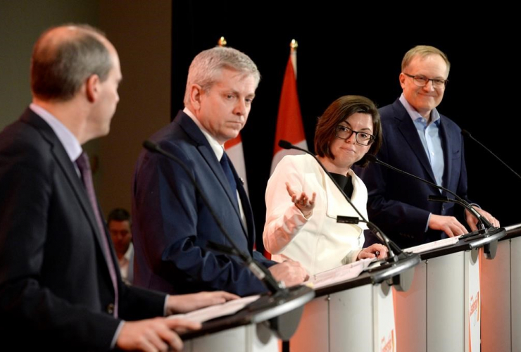 Niki Ashton, second from right, speaks with Guy Caron, left, as Charlie Angus and Peter Julian look on during the first debate of the federal NDP leadership race, in Ottawa on Sunday, March 12, 2017