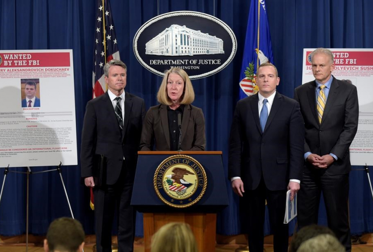 Acting Assistant Attorney General Mary McCord, second from left, speaks during a news conference at the Justice Department in Washington, Wednesday, March 15, 2017.