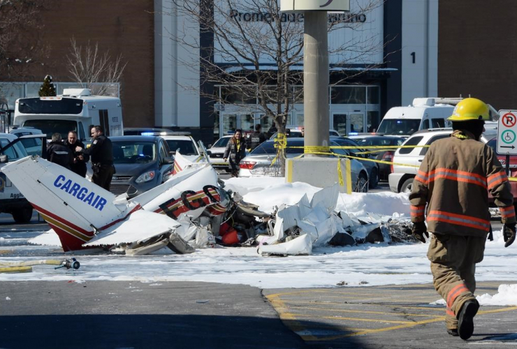 A firefighter and police officers look at the wreckage from a plane crash sits in a parking lot in Saint-Bruno, Que., on Friday, March 17, 2017. Two small planes have collided over a major shopping mall south of Montreal.