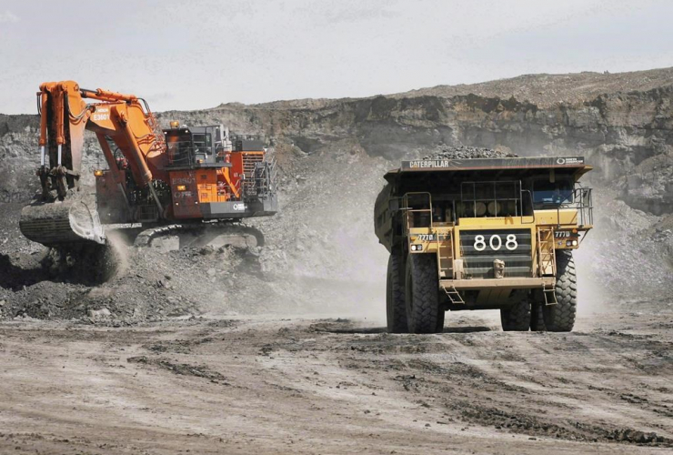 A haul truck carrying a full load drives away from a mining shovel at the Shell Albian Sands oilsands mine near Fort McMurray, Alta., on Monday.July 9, 2008