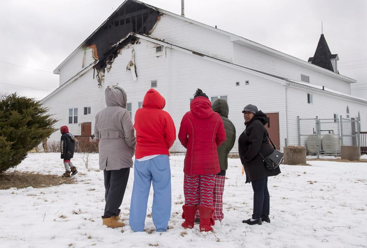 Members of the community look on as firefighters battle hotspots after a fire damaged St. Thomas Baptist Church in North Preston, N.S. on Wednesday, March 22, 2017. Officials say 10 trucks responded to the blaze that was contained to the rear of the struc