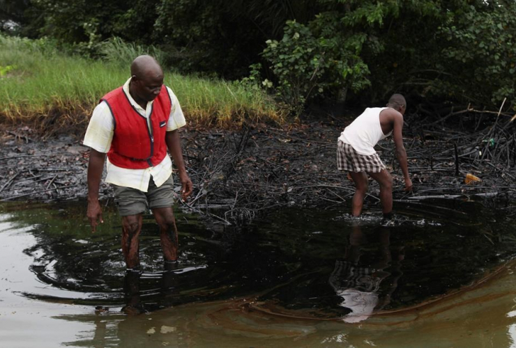 men walk in an oil slick covering a creek near Bodo City in the oil-rich Niger Delta region of Nigeria