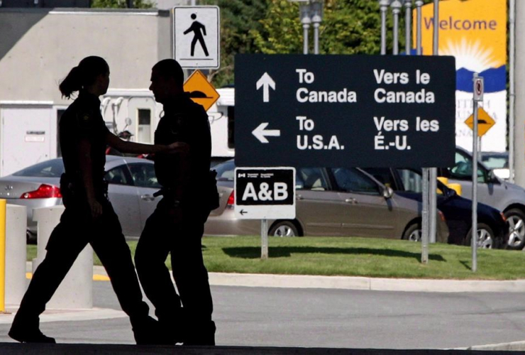 Canadian border guards are silhouetted as they replace each other at an inspection booth at the Douglas border crossing on the Canada-USA border in Surrey, B.C., on Thursday August 20, 2009.