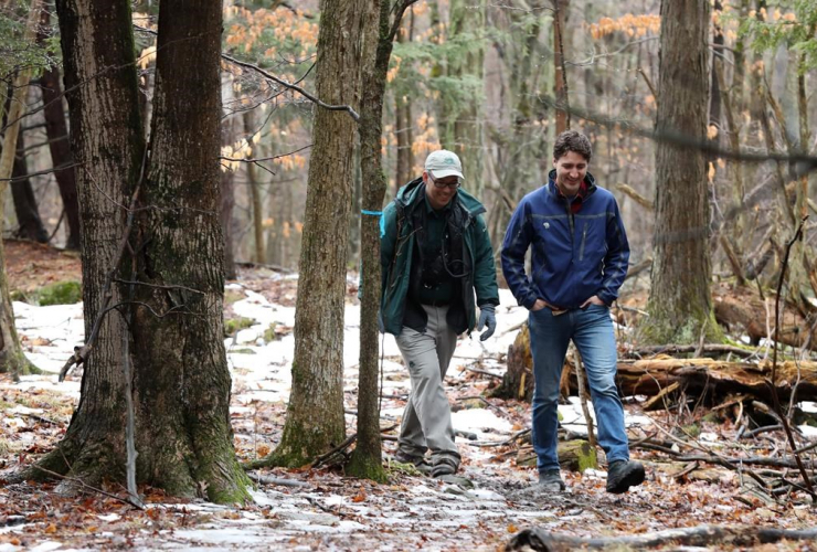 Prime Minister Justin Trudeau walks with Sheldon Lambert, Conservation manager with Parks Canada at the Landon bay in the Thousand Island National park in Gananoque, Ont., on Tuesday March 28, 2017.