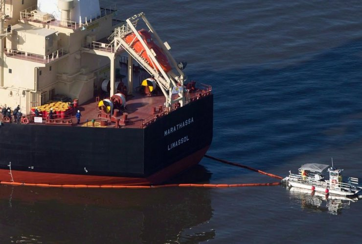 A spill response boat secures a boom around the bulk carrier cargo ship MV Marathassa after a bunker fuel spill in Vancouver, B.C., on April 9, 2015.
