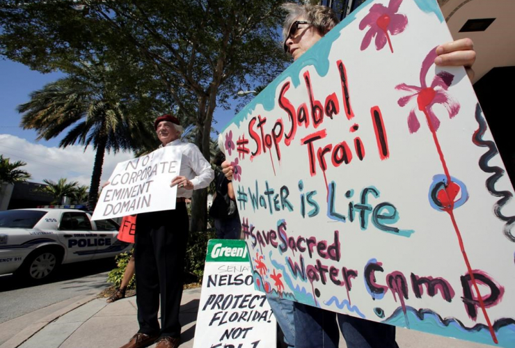 Sabal Trail pipeline protesters hold signs against the pipeline project in front of the office of U.S. Sen. Bill Nelson in Coral Gables, Fla.