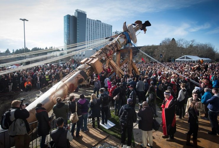 People gather to watch as a totem pole is raised in the spirit of reconciliation at the University of British Columbia in Vancouver, B.C., on Saturday, April 1, 2017.