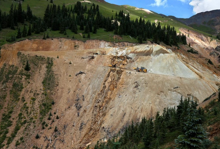 In this Aug. 12, 2015 photo, Environmental Protection Agency contractors use heavy machinery to repair damage at the site of the blowout at the Gold King Mine, which triggered a spill of toxic wastewater, outside Silverton, Colo.