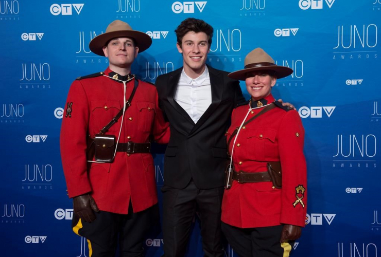 Shawn Mendes poses with RCMP constables Marie-Michele Ouimet and Zachary MacMillan as he arrives on the red carpet for the Juno Awards show in Ottawa, Sunday, April 2, 2017.