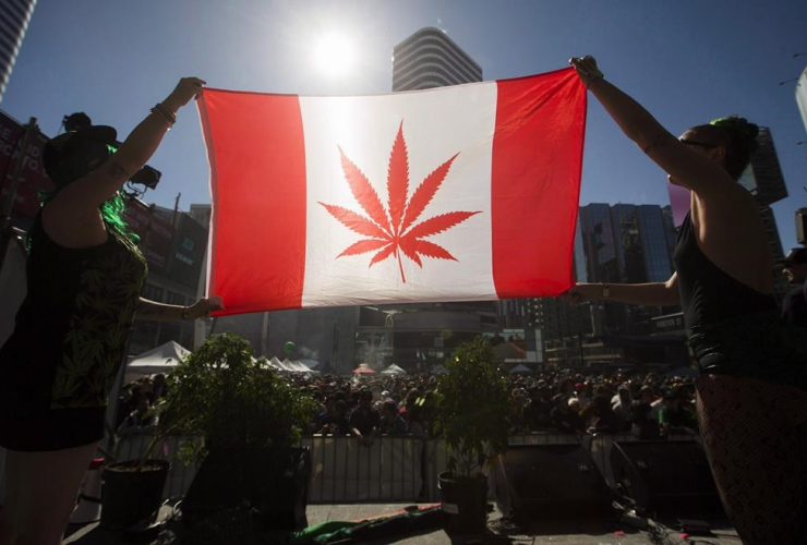 "Two people hold a modified design of the Canadian flag with a marijuana leaf in place of the maple leaf during the ""420 Toronto"" rally in Toronto, April 20, 2016."