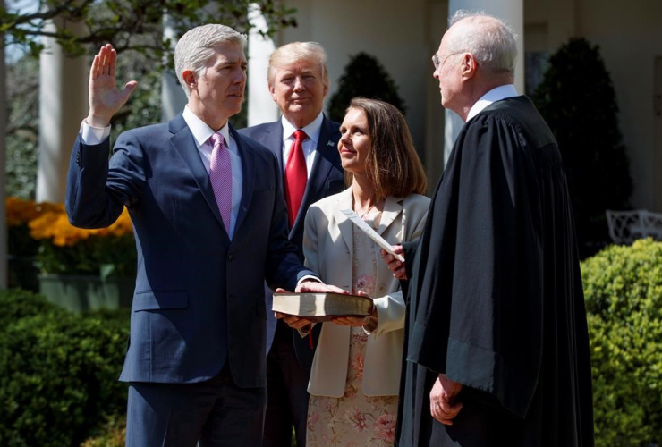 President Donald Trump watches as Supreme Court Justice Anthony Kennedy administers the judicial oath to Judge Neil Gorsuch during a re-enactment in the Rose Garden of the White House on April 10, 2017, in Washington.