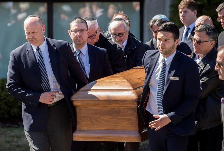 The coffin with the remains of Dr. Mark Wainberg is carried from the synagogue following his funeral in Montreal, Friday, April 14, 2017.