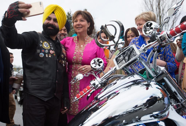 B.C. Liberal Leader Christy Clark, second left, poses for a selfie with a member of a Sikh motorcycle club during a Vaisakhi event at the Khalsa Diwan Society Sikh Temple in Vancouver, B.C., on Saturday, April 15, 2017.