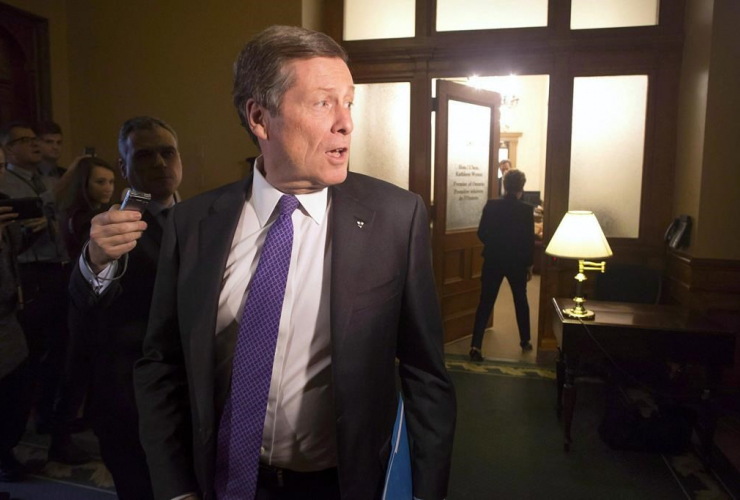 Toronto Mayor John Tory turns to answer a reporter's question as Ontario Premier Kathleen Wynne, right, walks back into her office following a meeting in Toronto on Monday, January 30, 2017.