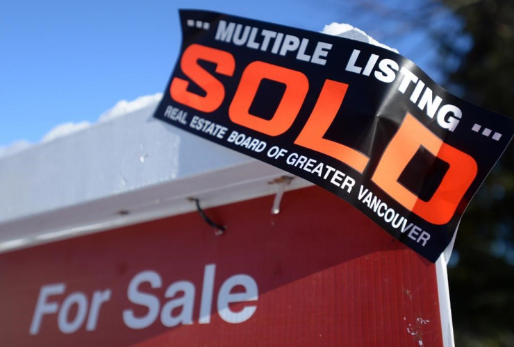 A real estate sold sign is shown outside a house in Vancouver, Tuesday, Jan.3, 2017.