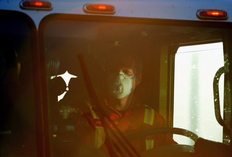 A firefighter wears a mask as he drives his truck pass a road block 16kms south of Fort McMurray, Alta., on Friday, May 6, 2016.