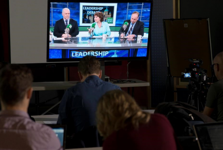 Reporters watch the British Columbia election leadership live radio debate with NDP Leader John Horgan, Liberal Leader Christy Clark and Green Party Leader Andrew Weaver on a television in Vancouver, Thursday, April 20, 2017.