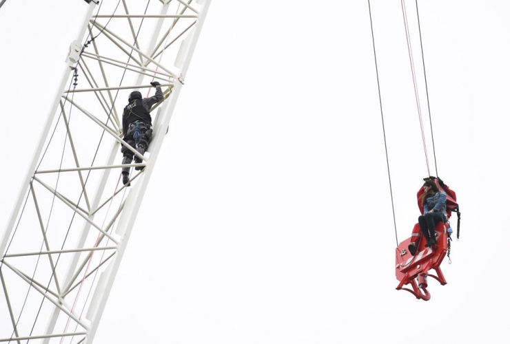 A woman is rescued from a downtown Toronto crane early Wednesday, April 26, 2017.