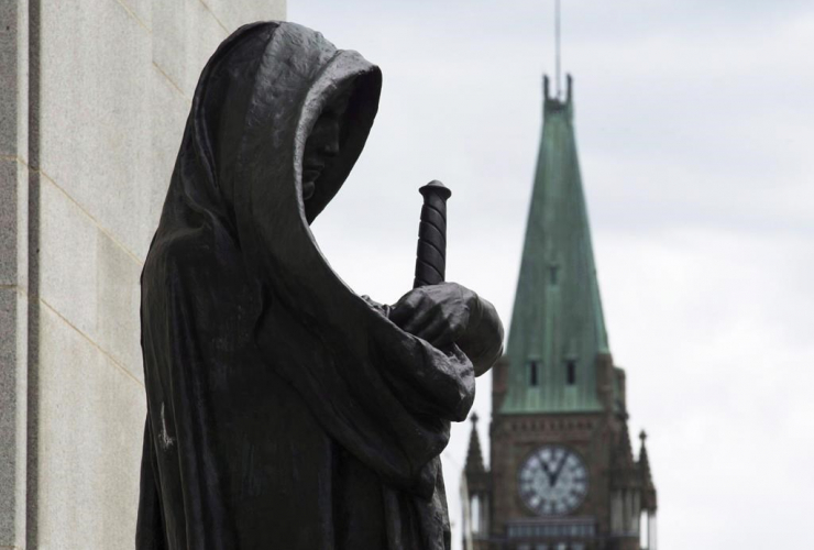 The Peace tower on Parliament Hill is seen behind the justice statue outside the Supreme Court of Canada in Ottawa, Monday June 6, 2016. File Photo by THe Canadian Press/Adrian Wyld