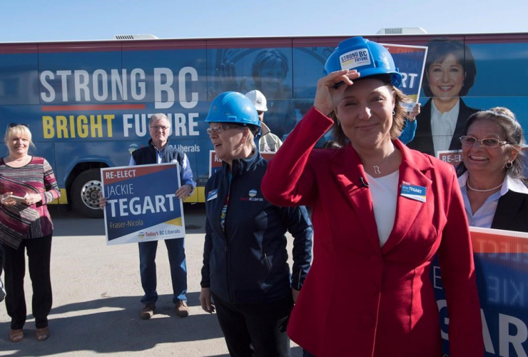 B.C. Liberal leader Christy Clark smiles as she adjusts her helmet during a tour of NMV Lumber in Merritt, B.C., Tuesday, May 2, 2017.