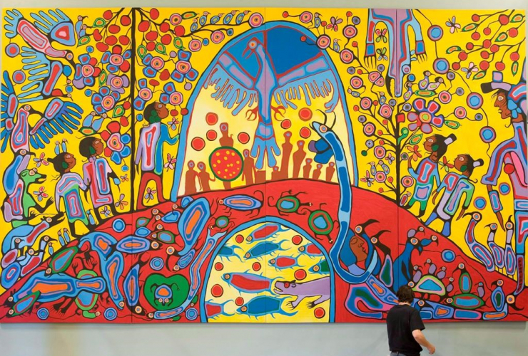"""A worker installs Canadian Aboriginal artist Norval Morrisseau's painting """"Androgyny"""" in the ballroom at Rideau Hall in Ottawa on Sept. 18, 2008. File photo by The Canadian Press/Adrian Wyld"""