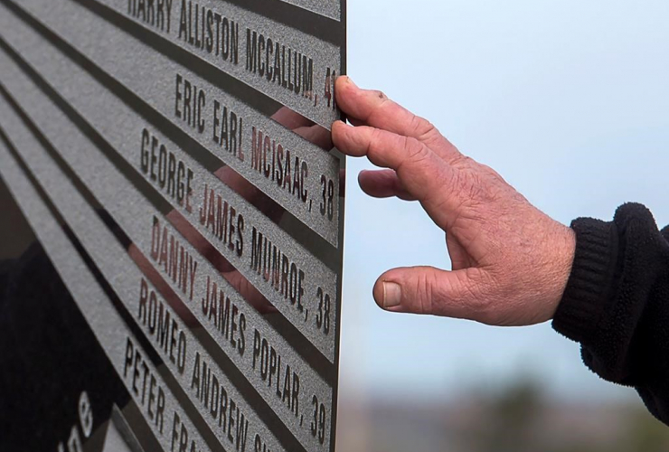 A hand touches the monument that honours the 26 coal miners who perished in the Westray mine disaster at the Westray Miners Memorial Park in New Glasgow, N.S. on Tuesday, May 9, 2017.
