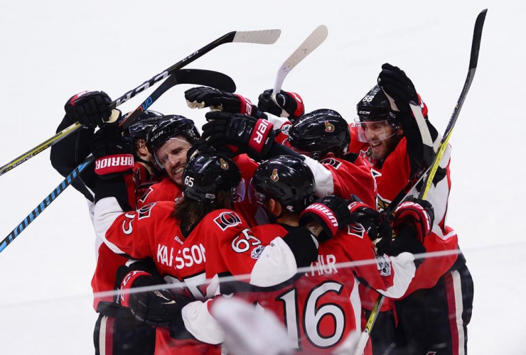 Ottawa Senators players celebrate after scoring against the New York Rangers late in the game during the third period in game five of a second-round NHL hockey Stanley Cup playoff series in Ottawa on May 6, 2017.