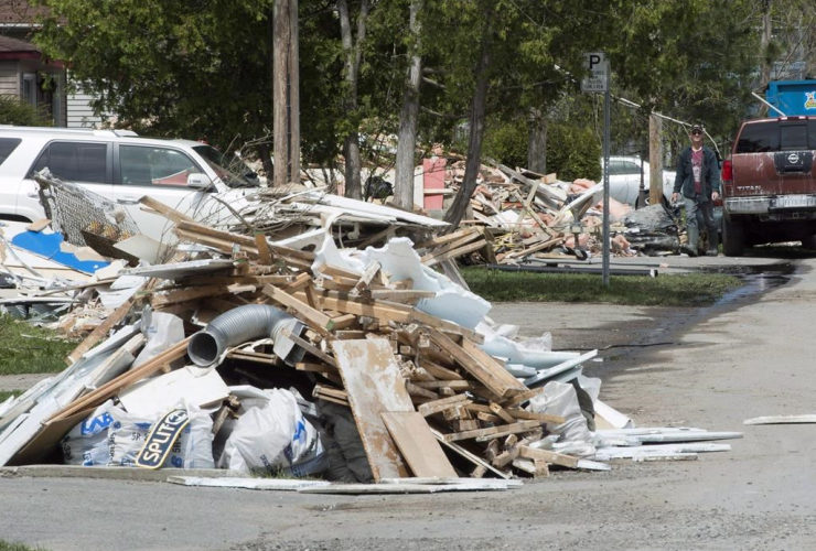Flood debris piles up on a street Monday, May 15, 2017 in Laval, Que. as residents clean up as the flood waters recede.