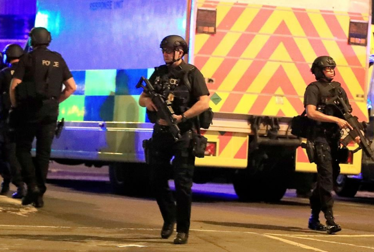 Armed police respond after reports of an explosion at Manchester Arena during an Ariana Grande concert in Manchester, England, Monday, May 22, 2017.