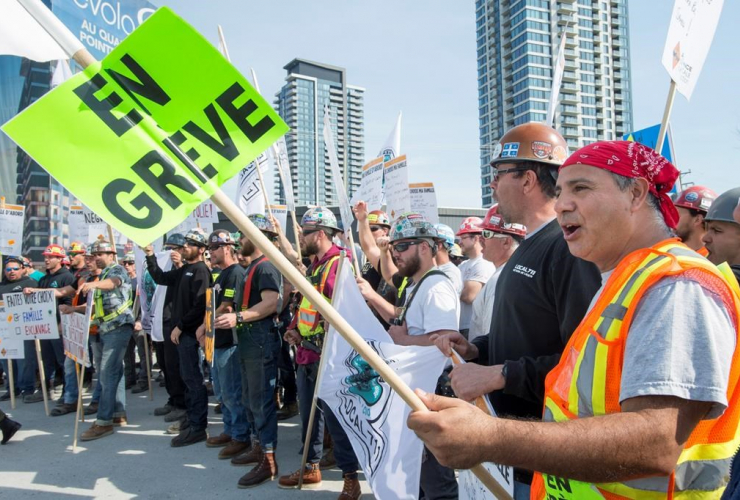 Construction workers form a picket line in front of a construction site on Wednesday, May 24, 2017 in Montreal.