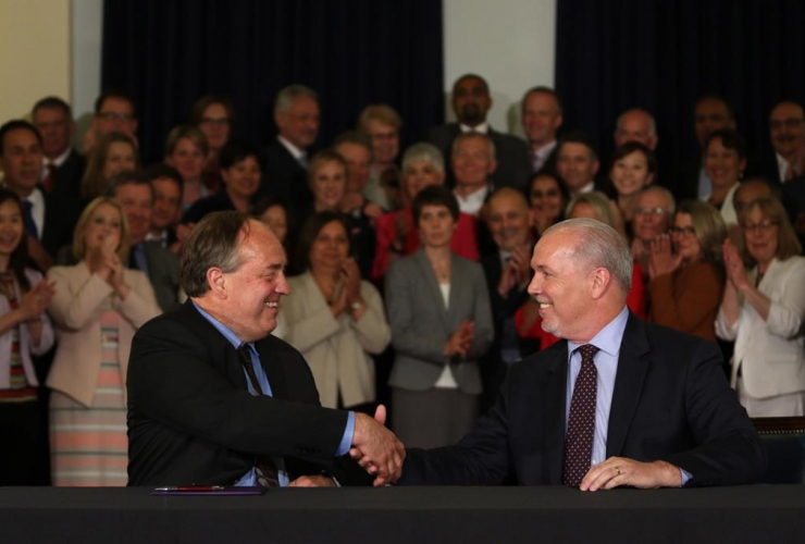 NDP leader John Horgan and Green party leader Andrew Weaver shake hands after signing an agreement on creating a stable minority government during a press conference in the Hall of Honour at Legislature in Victoria, B.C., on May 30, 2017.