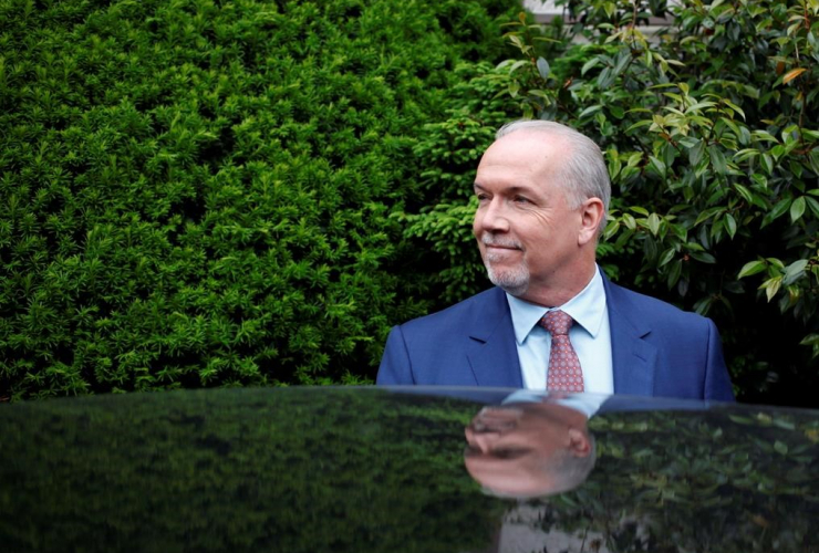 B.C. NDP leader John Horgan leaves with B.C. Green party leader Andrew Weaver from Government House after dropping of a signed document by 44 MLAs showing there is an agreement between the two parties in Victoria, B.C., on May 31, 2017.